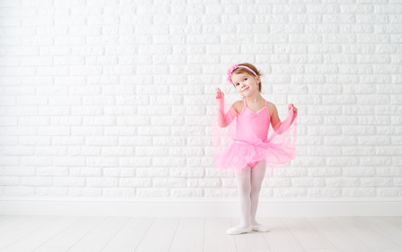Foto de little child girl dreams of becoming  ballerina in a pink tutu skirt - Imagen libre de derechos