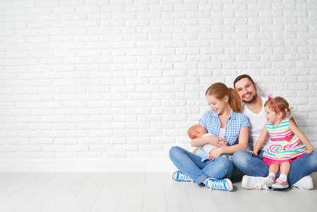 Photo pour happy family father mother and children sitting on the floor in an empty brick wall - image libre de droit