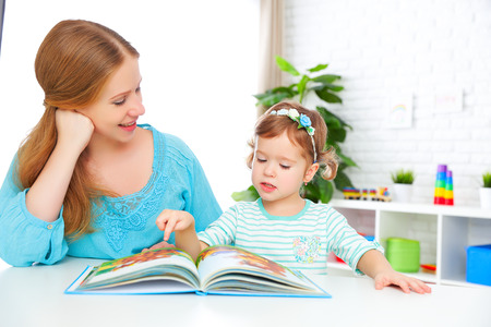 Photo pour mother and child reading a book together at home - image libre de droit