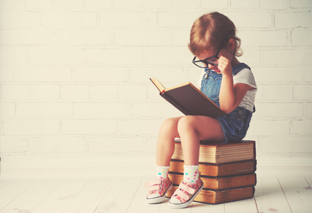 Photo pour happy child little girl with glasses reading a books - image libre de droit