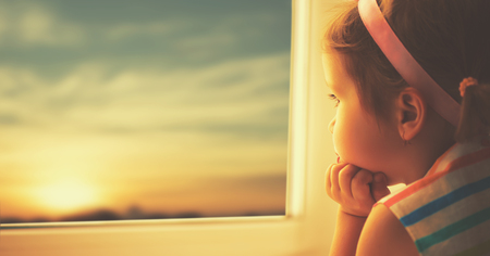Photo for child sad little girl looking out the window at the sunset - Royalty Free Image