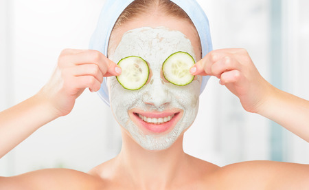 Photo pour Funny young girl with a mask for skin face and cucumbers on eyes - image libre de droit