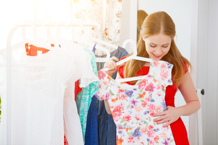 Photo for young woman in a red dress looks in the mirror and choose clothes - Royalty Free Image