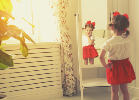 Photo for little girl child fashionista looking in the mirror at home in a red skirt, shoes of mother - Royalty Free Image