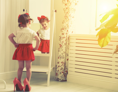 Photo pour little girl child fashionista looking in the mirror at home in a red skirt, shoes of mother - image libre de droit