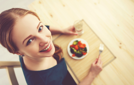 Photo pour young healthy woman eats vegetables at home in the kitchen summer - image libre de droit