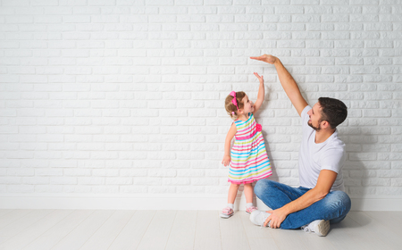 Photo pour concept. Dad measures the growth of her child daughter at a blank brick wall - image libre de droit