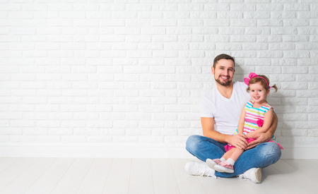 Foto de concept of mortgage housing problems. Family father child daughter at a blank white brick wall - Imagen libre de derechos