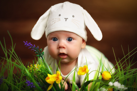 Foto de happy child baby dressed as the Easter bunny rabbit lying on the grass on the lawn with flowers - Imagen libre de derechos