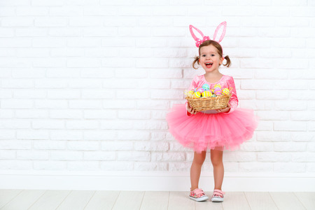 Photo for Happy child girl in a costume Easter bunny rabbit with ears and a basket of eggs - Royalty Free Image