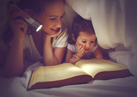Photo for Family reading bedtime. Mom and child daughter reading a book with a flashlight under the blanket in bed - Royalty Free Image