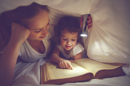 Foto de Family reading bedtime. Mom and child daughter reading a book with a flashlight under the blanket in bed - Imagen libre de derechos