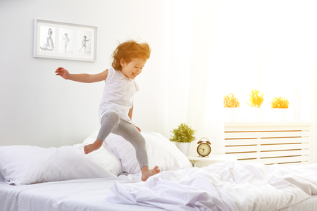 Photo pour happy child girl having fun jumps and plays bed - image libre de droit