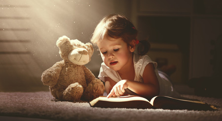 Photo for child little girl reading a magic book in the dark home with a toy teddy bear - Royalty Free Image