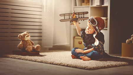 Photo pour concept of children's dreams and travels.  pilot aviator child with a toy airplane plays at home in his room - image libre de droit