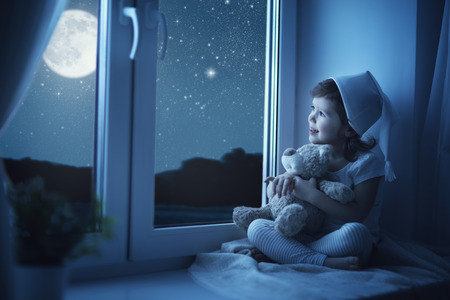 Photo for child little girl at the window dreaming and admiring the starry sky at bedtime night - Royalty Free Image