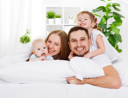 Photo pour happy family mother, father and two children at home in bed - image libre de droit