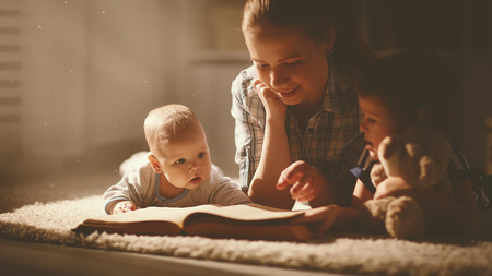 Photo pour happy family mother and children read a book in the evening at home - image libre de droit