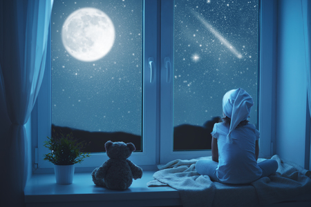 Foto de child little girl at the window dreaming and admiring the starry sky at bedtime night - Imagen libre de derechos