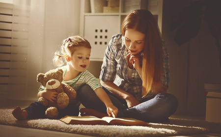 Photo pour happy family mother and daughter read a book in the evening at home - image libre de droit