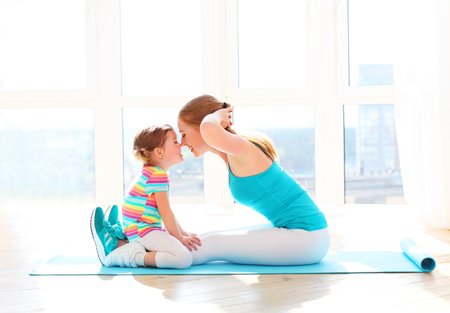 Photo pour family mother and child daughter are engaged in fitness, yoga, exercise at home - image libre de droit