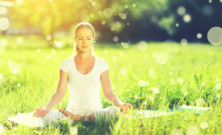 Photo for young woman enjoying meditation and yoga on green grass in the summer on nature - Royalty Free Image