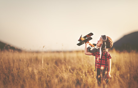 Foto de happy child dreams of traveling and playing with an airplane pilot aviator in outdoor in the summer - Imagen libre de derechos