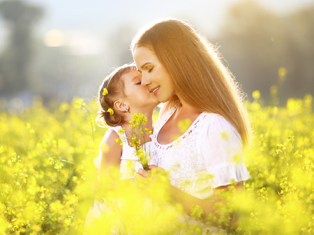 Photo pour Happy family on a summer meadow. little girl child daughter hugging and kissing mother - image libre de droit