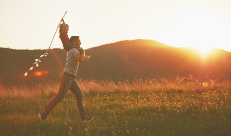 Foto de happy family father and child run on meadow with a kite in the summer on the nature - Imagen libre de derechos