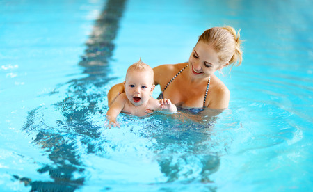 Foto de healthy family mother teaching baby swimming pool - Imagen libre de derechos