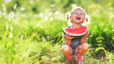 Foto de Happy child girl eats watermelon in the summer - Imagen libre de derechos
