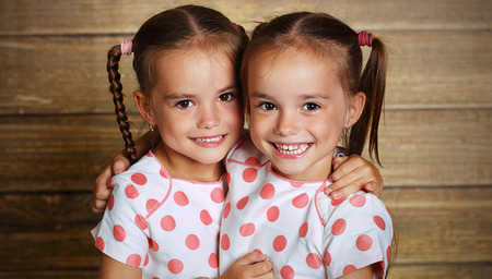 Photo for happy family children twin sisters hugging and laughing - Royalty Free Image
