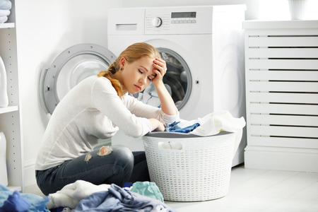 Photo pour tired unhappy woman housewife is engaged in the laundry, fold clothes into the washing machine - image libre de droit