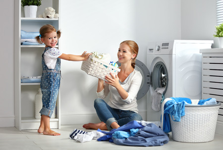 Foto de family mother and child girl little helper in laundry room near washing machine and dirty clothes - Imagen libre de derechos
