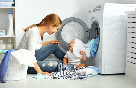 Photo pour mother a housewife with a baby engaged in laundry fold clothes into the washing machine - image libre de droit