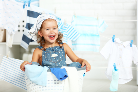 Photo pour child fun happy little girl  to wash clothes and laughs in the laundry room - image libre de droit