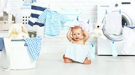 Foto de fun happy baby boy  to wash clothes and laughs in the laundry room - Imagen libre de derechos