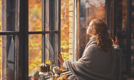 Foto de happy young woman enjoying the fresh autumn air at the open window - Imagen libre de derechos