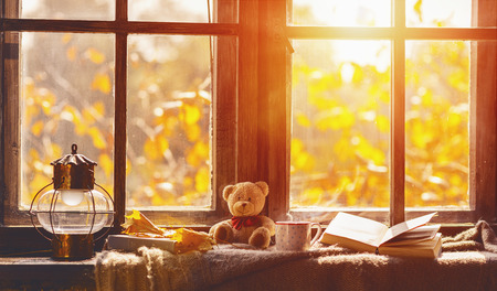 Foto de fall. cozy window with autumn leaves, a book, a mug of tea - Imagen libre de derechos