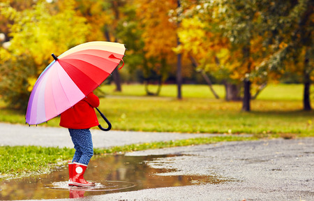 happy child girl with umbrella walking through the puddles after autumn rain