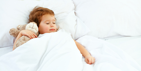 Photo pour child little girl sleeps in the bed with a toy teddy bear - image libre de droit