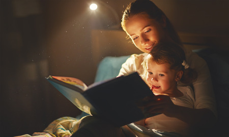 Photo pour mother and child girl reading a book in bed before going to sleep - image libre de droit