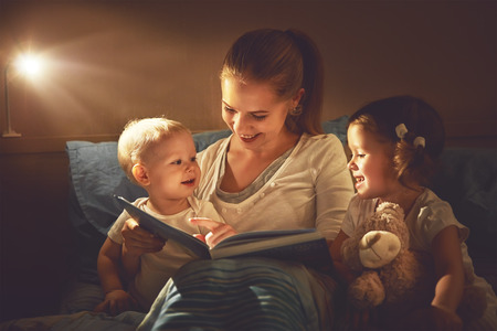 Photo pour happy family mother and children read a book in bed evening - image libre de droit