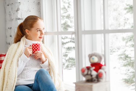 Photo pour happy young woman with cup of hot tea in winter window Christmas morning - image libre de droit