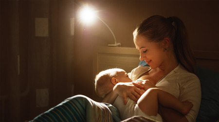 Photo pour breastfeeding. mother feeding a baby breast in bed dark night - image libre de droit