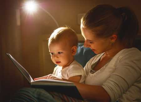 Photo pour mother and baby sonreading a book in bed before going to sleep - image libre de droit