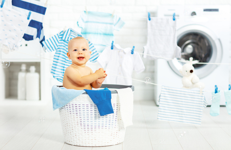 Photo for fun happy baby boy  to wash clothes and laughs in the laundry room - Royalty Free Image
