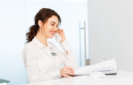 Photo for friendly young woman behind the reception desk administrator - Royalty Free Image
