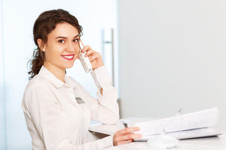 Photo pour friendly young woman behind the reception desk administrator - image libre de droit