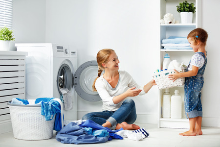 Photo pour family mother and child girl little helper in laundry room near washing machine and dirty clothes  - image libre de droit